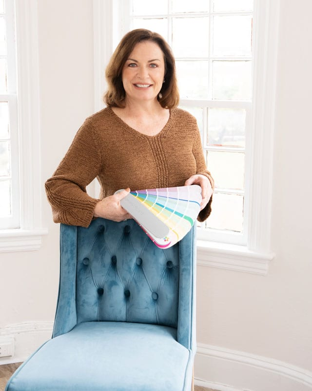 Nancy standing behind a wingback chair holding a swatch book of paint colors